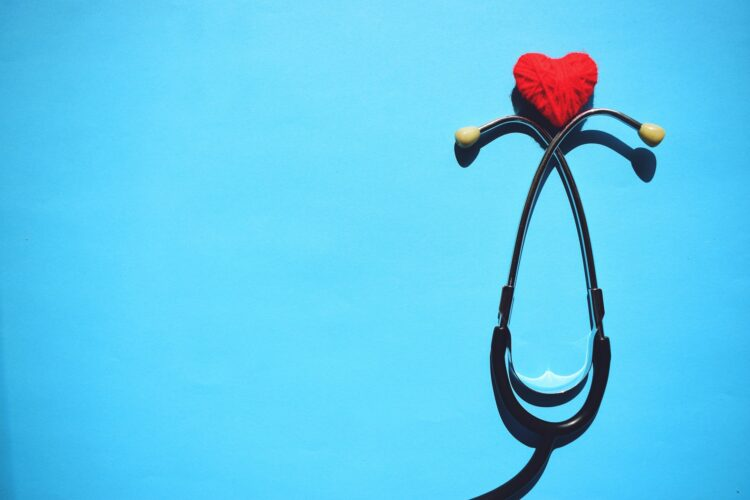 Medical stethoscope head and red heart