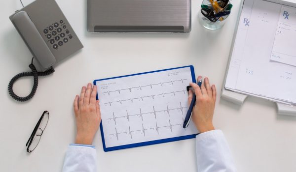 doctor hands with cardiogram at table